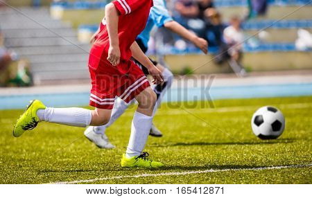Children Soccer Players Running with the Ball. Kids in Red Soccer Jerseys Playing Football on the Pitch. Sports Stadium in the Background