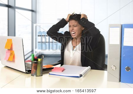 young beautiful latin businesswoman suffering stress working at modern office computer desk looking worried and desperate having problem pulling her hair at work in overwork concept