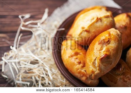 Delicious rustic pastries filled with meat and vegetables on a ceramic plate with wooden on a wooden background.