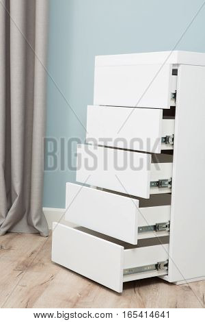 Wardrobe with many shelves opened in bedroom. Cupboard with five shelves of white color. Bedroom concept.