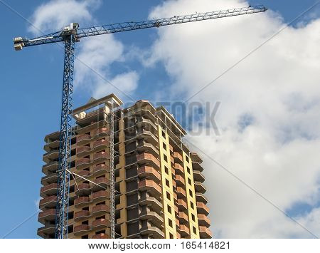 New high-rise building and crane in the background of the cloudy sky