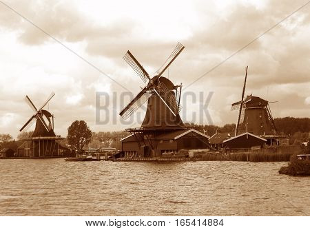 Sepia tone of three waterfront Dutch windmills under the cloudy sky, Zaanse Schans, Netherlands