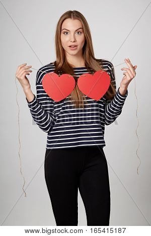 Excited surprised woman holding garland of two red paper hearts shape - blank copy space for letters or text