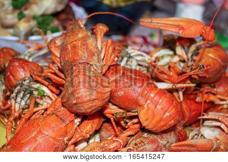 Red boiled crayfish on plate,  background with food