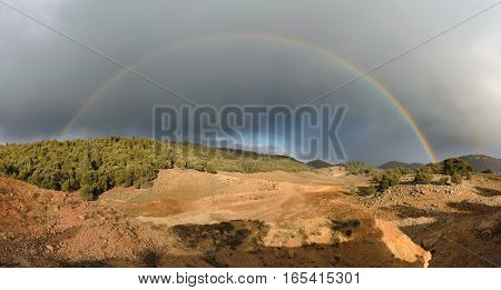 Panorama of a rainbow and dark clouds in the Ifrane National Park, Morocco.