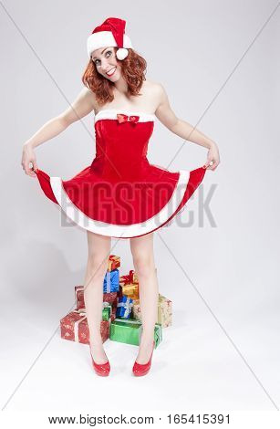 Holidays Concept and Ideas. Happy Smiling Caucasian Red Haired Santa Helper With LIfted Dress. Penty of Gifts Behind.Vertical Image