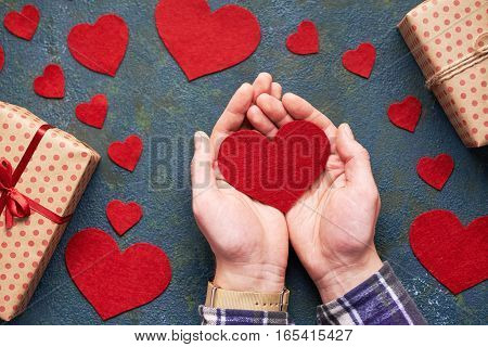 Heart in the men's hands of love. Concrete background with hearts and gifts on Valentine's Day. Symbol of love. The concept of a romantic Valentines Day. Flat lay. Top view table.