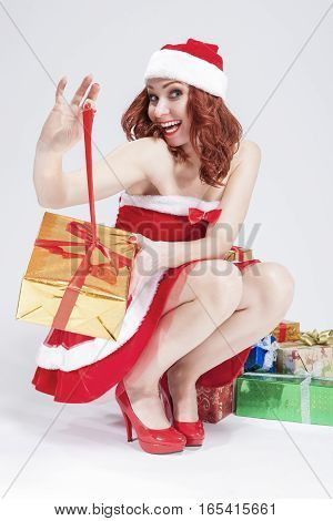 Christmas and New Year Concept and Ideas. Positive Caucasian Santa Helper Girl Unwrapping Golden Gift with Red Ribbon. Against White. Vertical Image