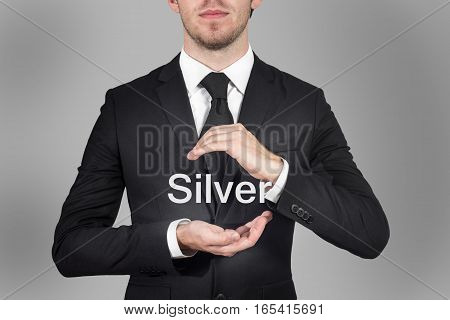 businessman in suit protecting word silver with hands