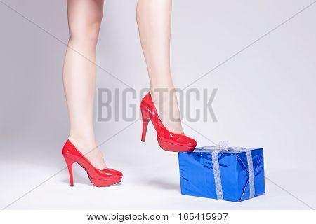 Closeup of Sexy Legs of Caucasian Woman on Posing in High Heels. Touching Wrapped in Blue Gift with Shoes.Against Whie. Horizontal Image