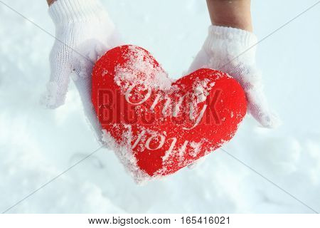 Hands in warm white gloves holding red heart on snowy background.