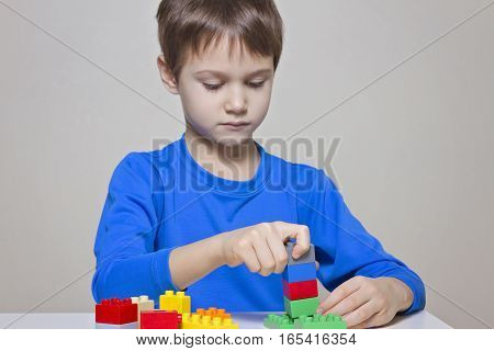 Little kid boy playing with colorful plastic construction toy blocks at the table. Children, education, toys, leisure concept