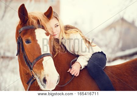 Young rider girl with long hair relaxing on horse neck. Friendship background. Warm color toned image