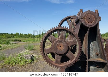 Rusting industrial equipment with gears. Part of an abandoned copper mine that is now a Historic National Park in Upper Michigan. Lots of texture and detail. Copy space in sky if needed.