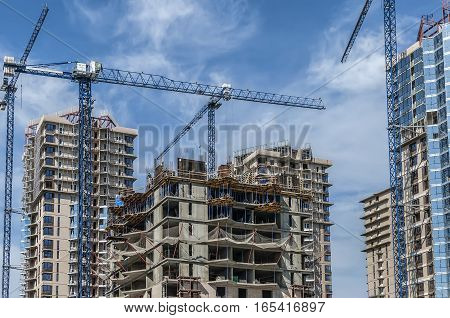 The complex of buildings under construction and blue tower cranes against the sky
