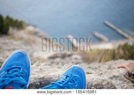Pair of sneakers on background of mountains and sea, blurred background