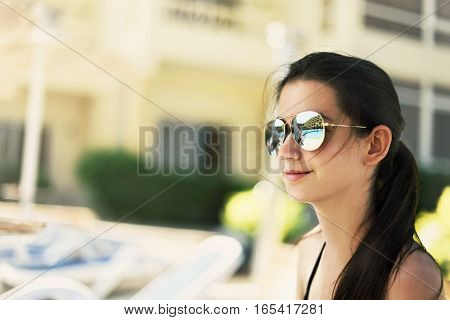 tinted image pretty smiling girl sitting a poolside. swimming pool and the hotel building are reflected in her sunglasses. horizontal orientation