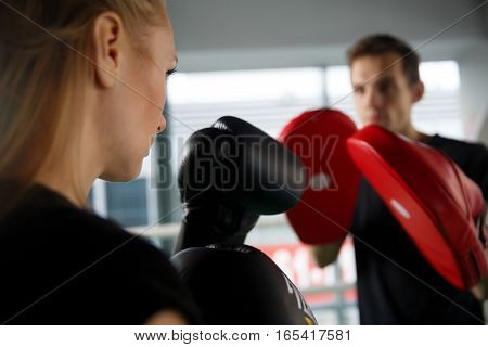 Beautiful girl with guy boxing in sports hall