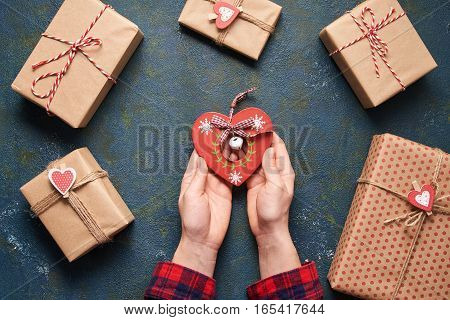 Close up on female hand holding a wooden heart toy presents for valentine day. Flat lay. Top view table. Valentines day background with a gift boxes on concrete board.