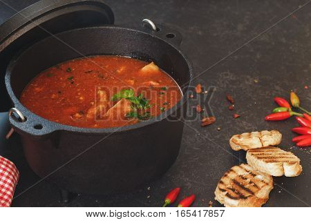 Fish and tomato stew in cast iron pot with grilled bread slices on rustic table. Macro, selective focus