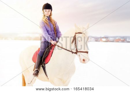 Young girl in helmet riding white horse on winter field