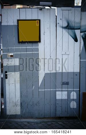 A shaky construction site door with a wooden fence forms a construction site barrier.