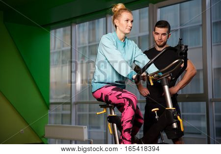 Trainer instructs sportswoman on simulator in gym