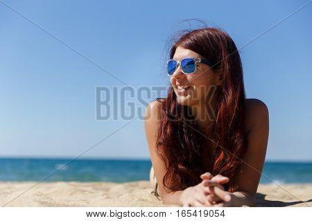 Girl lying on sandy beach near sea