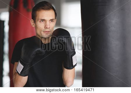 Portrait of young athlete in boxing bag in hall