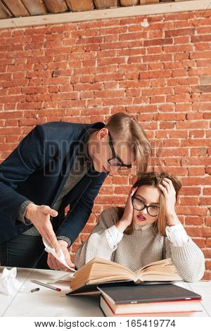 Scared student girl listening to teacher. Shocked of ability of information young woman having headache, free space. Education, problems, stress concept