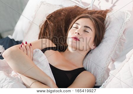 Beautiful woman sleeping with crossed hands. Portrait of young girl hugging herself while dreaming alone in bed. Loneliness, frost, bedroom, broken heating concept