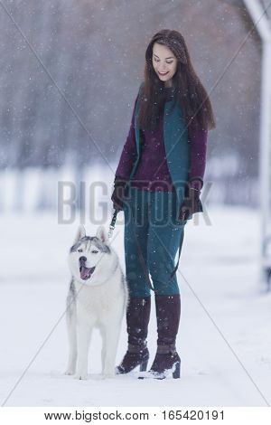 Portrait of Pretty Smiling Woman Walking with Her Dog Outside. Vertical Image Composition