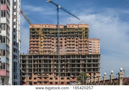 Building under construction in red brick and three construction crane