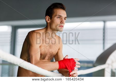 Young man in boxing ring in sports hall