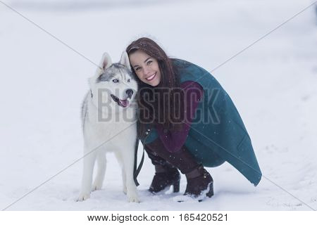 Portrait of Pretty Smiling Woman Hugging Her Husky Dog Outside. Horizontal Image Composition