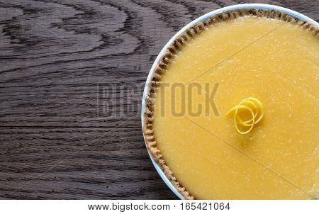 Lemon tart on the wooden background: top view