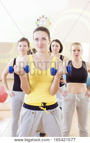 Female Fitness Teamwork Concepts. Group of Four Athletes Exercising with Barbells Indoors. Vertical Image