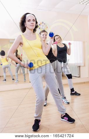 Three Caucasian Females Having a Workout Training with Barbells Indoors. Vertical Image Orientation