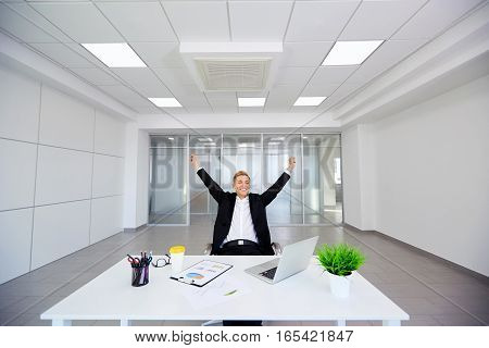 The concept of business winning, luck, dreams, happiness. Blond businessman in a modern office raised his hands up.