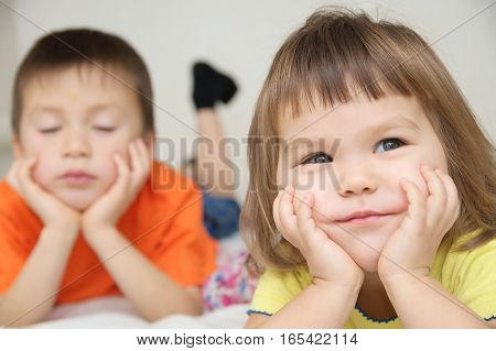 smiling little girl with cute cheeks and her brother lying on bed happy one and unhappy one