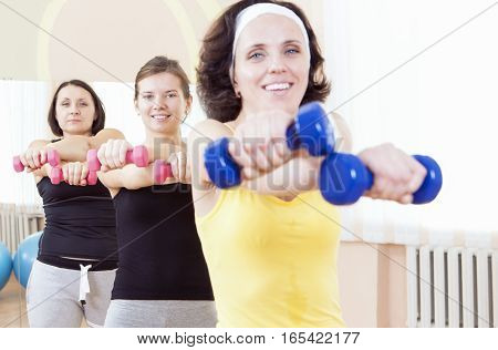 Sport and Fitness Ideas. Group of Three Caucasian Female Athletes Having a Workout Training with Barbells Indoors. Horizontal Image Composition