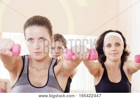 Three Caucaisan Fitness Girls Having a Workout With Barbells Indoors. Horizontal Image Composition