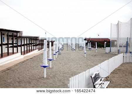 Empty beach with covered lounge chairs. Italy