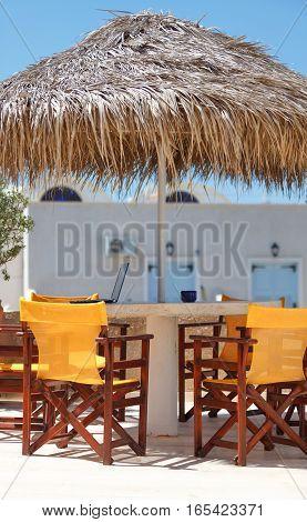 Hotel balcony terrace with straw umbrella and bright chairs. Perissa Santorini island Greece