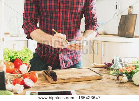 Ingredients for cooking healthy food on a wooden table in a home kitchen. In the background a man writes a recipe to notebook