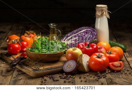 Variety food on a wooden table. Vegetables fruit milk and oil on a wooden table on a dark background