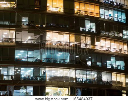 Window of the multi-story building of glass office lighting and working people within. Windows office building for background. People working late.
