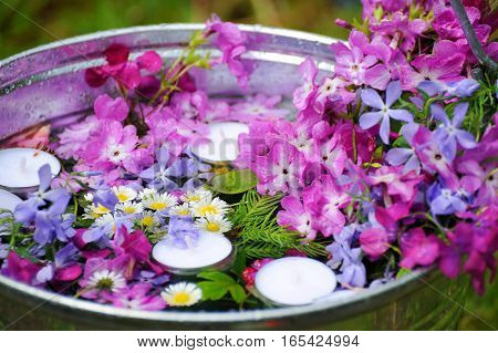 Composition with pink flowers in water containers and candles