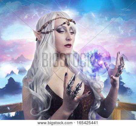 Elf girl photo. Beautiful elf girl holding a magic ball on fantasy background photo.