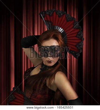Spanish dancer. A girl dancing spanish dance with folding fans on red curtain background photo.